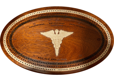 Custom bloodwood cribbage board with inlaid and carved medical symbol